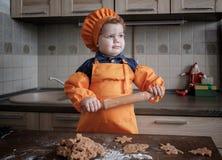 De leuke Europese jongen in een kostuum van de kok maakt gemberkoekjes stock foto's