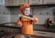 De leuke Europese jongen in een kostuum van de kok maakt gemberkoekjes royalty-vrije stock afbeeldingen