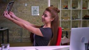 De leuke gember Kaukasische vrouw heeft videogesprek over tablet terwijl het zitten bij Desktop dichtbij computer, koelen, in kwe stock videobeelden