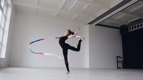 De leuke gymnastiek in zwart lichaam voert de gymnastiekoefening met een gekleurd lint in de witte studio uit Leuk meisje stock videobeelden