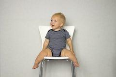 De leuke het glimlachen zitting van de babyjongen op een witte stoel tegen een grijze achtergrond Stock Fotografie