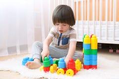 De leuke 2 jaar jongens speelt thuis plastic blokken Stock Fotografie