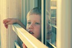 De leuke 7 jaar oude jongens kijkt uit het venster Royalty-vrije Stock Foto's