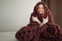 De leuke jonge die vrouw zit op het bed in een grote en pluizige bruine plaid wordt verpakt Warmte en comfort van huis stock afbeeldingen