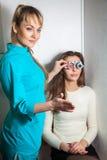 De leuke jonge donkerbruine vrouw controleert visie in een oftalmoloogwi stock afbeelding