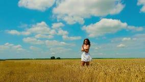 De leuke jonge donkerbruine vrouw met mooi lang haar en de witte korte zomer sundress loopt op gouden tarwegebied stock videobeelden