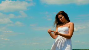 De leuke jonge donkerbruine vrouw met mooi lang haar in de witte korte zomer sundress houdt tarweoren in haar handen stock video