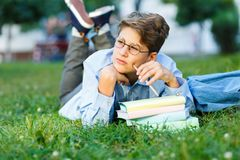 De leuke, jonge jongen in ronde glazen en het blauwe overhemd schrijven met zijn linkerhand terwijl het liggen op het gras in het royalty-vrije stock fotografie