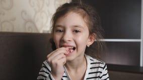 De leuke jonge meisjes en schudt haar losse tand in een inspanning waggelt om het te verwijderen stock video