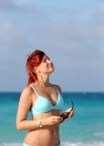 De leuke jonge roodharigevrouw geniet van zon bij de oceaankust Royalty-vrije Stock Foto's