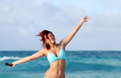 De leuke jonge roodharigevrouw geniet van zon op de sh oceaan Stock Afbeeldingen