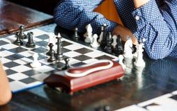 De leuke jonge slimme jongen in blauw overhemd speelt schaak op de opleiding vóór de toernooien het kamp van de schaakzomer hobby stock fotografie
