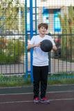 De leuke jonge sportieve jongen in witte t-shirt speelt basketbal op zijn vrije tijd, vakantie, de zomerdag op de sportengrond Sp stock afbeelding