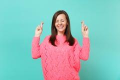 De leuke jonge vrouw in gebreide roze sweater die vingers gekruiste ogen gesloten houden maakt wens die op blauwe muurachtergrond stock afbeeldingen