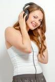 De leuke jonge vrouw luistert aan hoofdtelefoons Stock Afbeeldingen