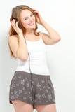 De leuke jonge vrouw luistert aan hoofdtelefoons Royalty-vrije Stock Afbeeldingen
