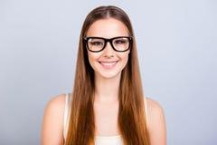De leuke jonge vrouwelijke student is in modieuze zwarte glazen, het dragen royalty-vrije stock afbeeldingen