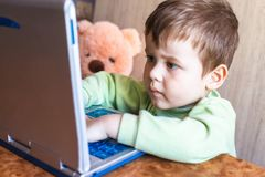 De leuke jongen duwt laptops toetsenbord en hij bekijkt het scherm royalty-vrije stock fotografie