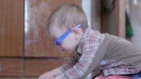 De leuke jongen in grappige glazen trekt thuis met beide handen op papier stock videobeelden