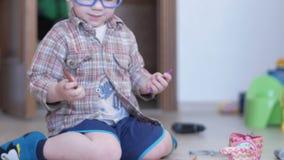 De leuke jongen in grappige glazen trekt thuis met beide handen op papier stock footage