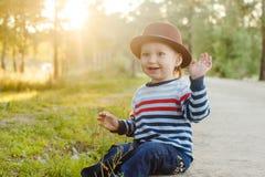 De leuke jongen in hoed zit in een licht van de Parkzonsondergang royalty-vrije stock afbeelding
