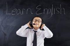 De leuke jongen leert het Engels met hoofdtelefoons Royalty-vrije Stock Fotografie