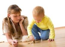 De leuke jongen met moeder leert om geld thuis te tellen stock afbeeldingen
