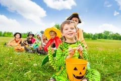 De leuke jongen in monsterkostuum houdt Halloween-emmer Royalty-vrije Stock Foto's