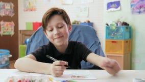 De leuke jongen trekt beeld van zijn familie met viltpennen stock footage