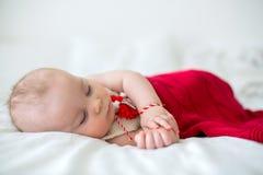 De leuke jongen van de babypeuter, die met witte en rode armband slapen Stock Foto's