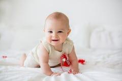 De leuke jongen van de babypeuter, die met witte en rode armbanden spelen Stock Afbeelding