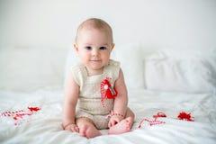 De leuke jongen van de babypeuter, die met witte en rode armbanden spelen Royalty-vrije Stock Afbeeldingen