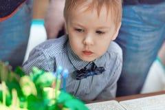 De leuke Kaukasische blondejongen blaast uit de kaarsen op de verjaardagscake royalty-vrije stock foto's