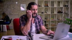 De leuke Kaukasische creatieve zakenman spreekt over telefoon en typt op toetsenbord het koelen, werkend vibes en bureau stock footage