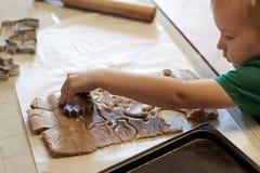 De leuke Kaukasische hulp van de babyjongen in keuken, die eigengemaakte coockies maken Toevallige levensstijl in huis binnenland stock fotografie