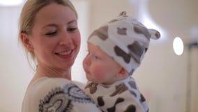 De leuke Kaukasische vrouw houdt baby in handen en bekijkt camera met glimlach stock videobeelden