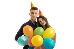 De leuke kerel met een meisje die met kegels op hun hoofden camera bekijken die en houdt veel gekleurde ballen glimlachen Stock Foto