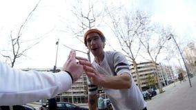 De leuke kerelfietser die oranje die GLB dragen wordt door vrienden wordt toegejuicht dat zijn hand raakt stock videobeelden