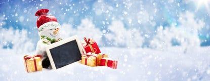 De leuke Kerstmissneeuwman met stelt op de Sneeuw voor Stock Afbeelding