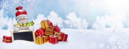 De leuke Kerstmissneeuwman met stelt op de Sneeuw voor Stock Foto's
