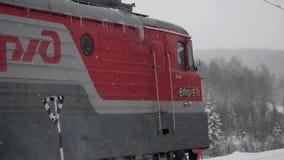 De leuke Kerstmistrein gaat door fantastisch de winterbos in slowmotion tijdens sneeuwval 1920x1080 stock videobeelden