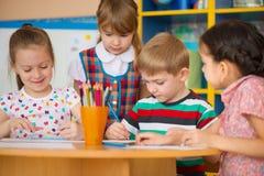 De leuke kinderen bestuderen bij opvang Stock Foto