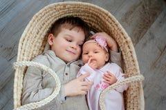 De leuke kinderen, weinig jongen 5 jaar oud, met hem pasgeboren zuster ligt in een rieten wieg royalty-vrije stock afbeeldingen