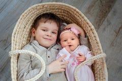 De leuke kinderen, weinig jongen 5 jaar oud, met hem pasgeboren zuster ligt in een rieten wieg stock afbeelding