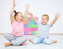 De kinderen zitten op vloer Stock Foto
