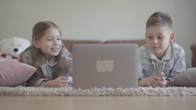 De leuke kleine tweelingenjongen en het meisje liggen bij het tapijt en het letten van op iets grappig op de computer, het lachen stock videobeelden