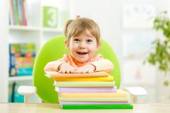 De leuke kleuter van het jong geitjemeisje met boeken stock foto's