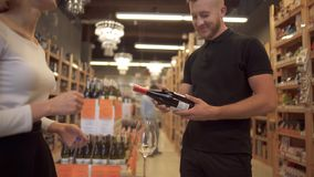 De leuke kortharige meisjesverkoper biedt wijn aan de bezoeker aan De mannelijke die koper neemt een fles wijn door de verkoper w stock videobeelden