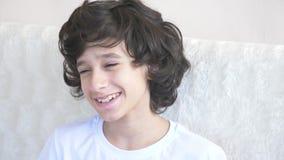 De leuke krullend-haired jongen de tiener onderzoekt de camera lachend en maakt een grappige gelaatsuitdrukking 4k, langzame moti stock videobeelden