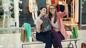 De leuke meisjes nemen selfie in winkelcomplex het stellen met document zakken en in handgebaren aanwezig zijnd op bank stock footage